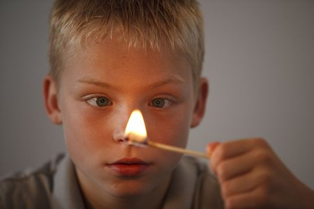 teens playing: Young boy playing with fire and match sticks