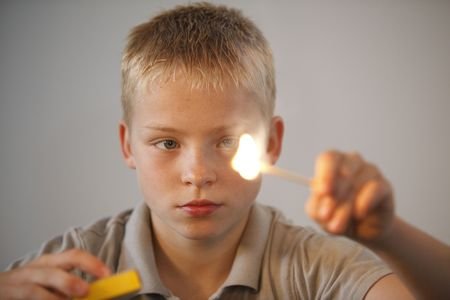 Young boy playing with fire and match sticks photo