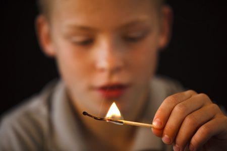 火とマッチと遊ぶ若い男の子を棒します。