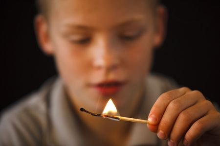 Young boy playing with fire and match sticks