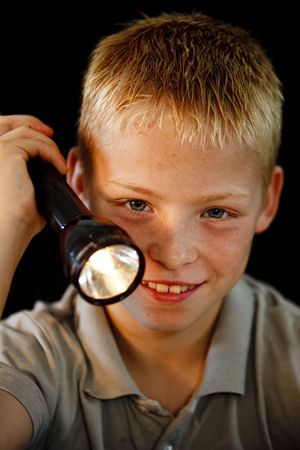 Young boy playing with a flashlight