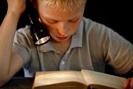 Young boy reading a book with a flashlight in his hand photo