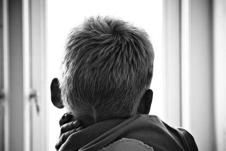 雨の日に、窓を見る若い男の子 写真素材