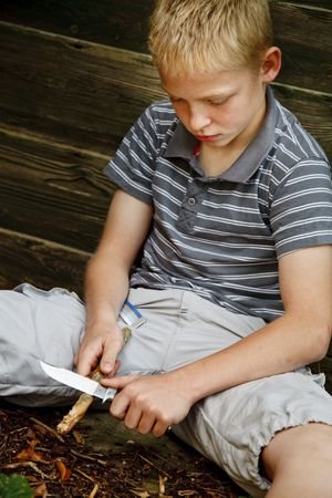 Young boy cutting in a stick with a knife photo
