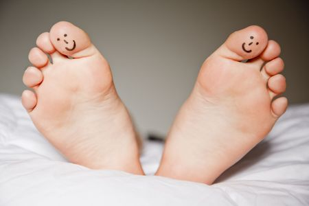 Feet of boy in bed with smiley faces on two of the toes photo