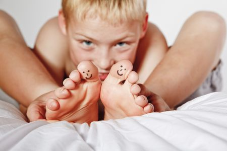boy feet: Portrait of young boy in his bed with smiley faces painted on two of his toes Stock Photo