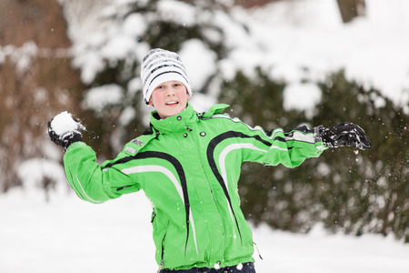 glee: Young boy throwing snowballs during a winter snow fight smiling with glee as he takes aim in a winter landscape