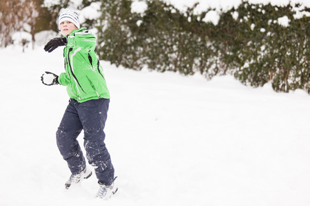 retaliation: Young boy in warm winter clothing enjoying a winter snowball fight as he takes aim at the camera with a snowball with standing in pristine white snow, with copyspace to the right