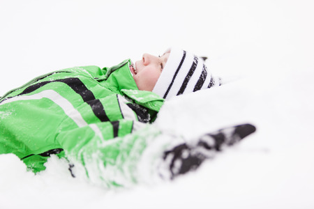 Young child relaxing lying on the fresh white winter snow looking up into the air with a happy grin of enjoyment, upper body profile view in warm winter clothing Stock Photo