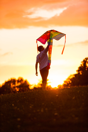 Silhouette of a boy carrying a kite against a dramatic orange sunset sky holding it above his head as her prepares to launch it
