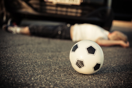 Young boy playing soccer hit by a car lying in the street in front of the bumper of the car with his ball in focus in the foreground