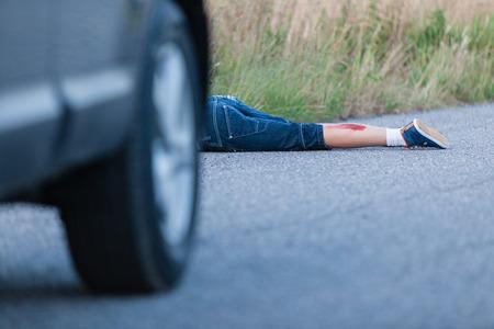 Gewonde Benen van een Jongen aangereden door een eigen auto liggen achter het voertuig op de rijbaan
