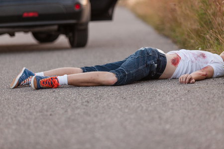 traffic accidents: Young boy run over by a car lying face down in the road bleeding from his injuries with a car with an open door visible behind