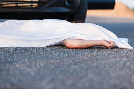 Body of a young child covered by a sheet lying on the street in front of the bumper of the car that ran him over with foreground copyspace
