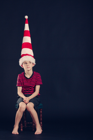 dunce cap: Young boy in a red and white striped dunce cap sitting barefoot in the corner with a dejected expression over a dark background with copyspace