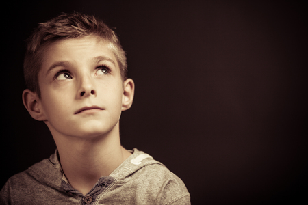 Serious young boy sitting thinking looking up into the air with a pensive expression, head and shoulders over a dark background with copyspace