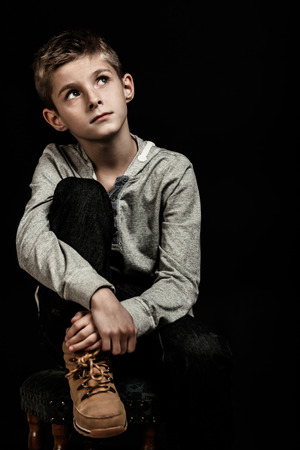 knee boots: Pensive young boy sitting thinking looking up into the air with a serious expression as he jugs his knee, over a dark background