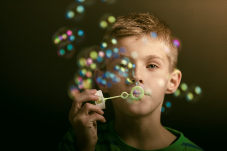 shadowy: Young boy blowing iridescent soap bubbles at a party or celebration, close up with selective focus to his face in shadowy darkness