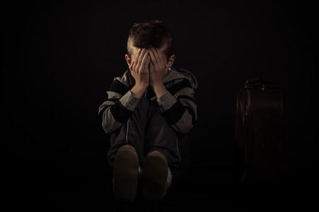 Scared Boy Sitting on the Floor Inside the House and Covering his Face Against Dark Background.