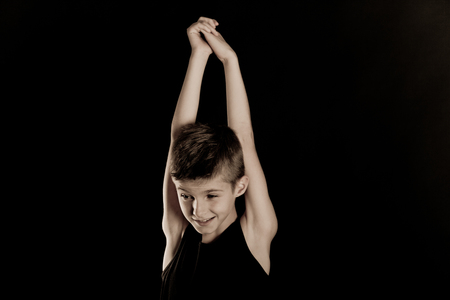 lithe: Smiling Slim Boy Raising his Arms Straight While Looking Into the Distance Against Black Background with Copy Space.