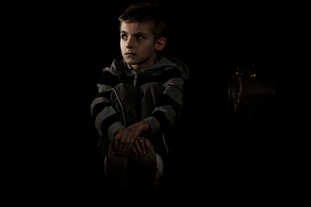hugging knees: Thoughtful Boy Sitting on the Floor and Holding his Feet with Arms Crossed, Looking Into the Distance Against Black Background.