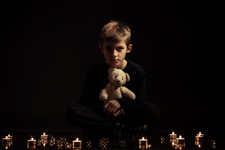 lighted: Serious Boy Holding his Teddy Bear Stuffed Toy Sitting on the Floor with Lighted Candles Against Black Background. Stock Photo
