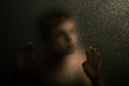 leaning by barrier: Close up Scary Young Boy with Blurry Face Trap Behind a Barrier, Leaning Against a Textured Glass Wall and Showing his Hands. Stock Photo