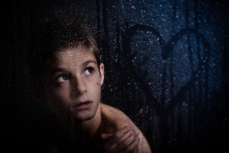 sombre: Close up Thoughtful Young Boy Looking at the Heart Shape Drawing on Misty Glass Wall Against Dark Background. Stock Photo