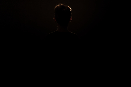 facing backwards: Silhouette of a Young Schoolboy in Standing Position Facing Backwards with Copy Space Stock Photo