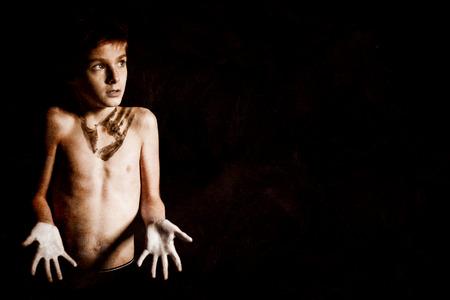 niño sin camisa: Muchacho sin camisa ni idea con la impresión de la mano en el pecho, mirando en la distancia contra el fondo Negro con espacio de copia.