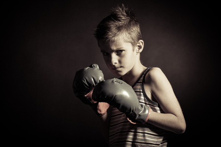 pugilist: Close up Boxer Boy Wearing Hand Gloves and Looking Fierce at the Camera Against Black Background. Stock Photo