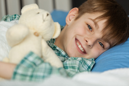 recuperating: Close up Happy Handsome Young Boy with his Teddy Bear Stuffed Toy Lying on his Bed and Smiling at the Camera.