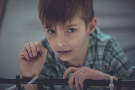 inhumane: Close up Abused Young Boy Tied on Bed Rail Inside his Room and Looking Straight at the Camera Stock Photo