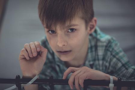 Cierre de niño abusado joven atado en el carril cama en su habitación y mirando directamente a la cámara