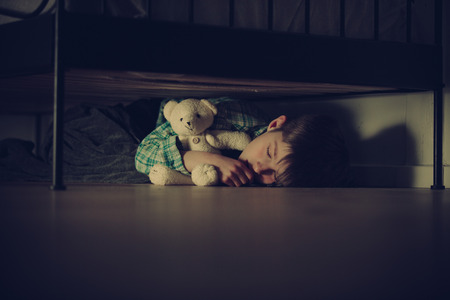 fear child: Scared Young Boy Sleeping Under his Bed Inside his Room While Hugging his Teddy Bear Stuffed Toy at Night.