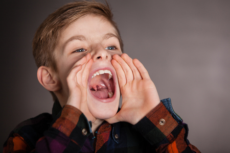 mouth close up: Close up Good Looking Young Boy Yelling Into the Distance with Mouth Wide Open Against Gray Background