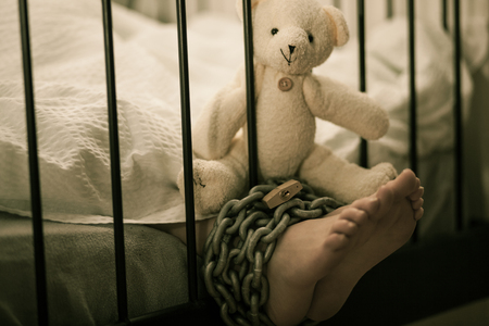 Teddy Bear Stuffed Toy on Top of the Feet of a Young Boy Tied with Chain and Lock While Sleeping on his Bed.