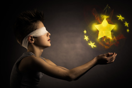 supernatural power: Glowing Yellow Stars Over the Open Hands of a Blind Boy with Bandage on his Eyes Against Gray Background.