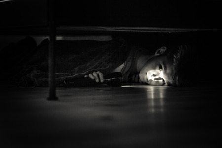Sad Young Boy Holding a Flashlight, Lying Under his Bed Inside his Room and Looking at the Camera in Monochrome Color.