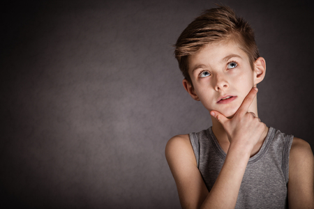 Close up Thoughtful Young Boy Looking Up with Hand on the Face Against Gray Background with Copy Space