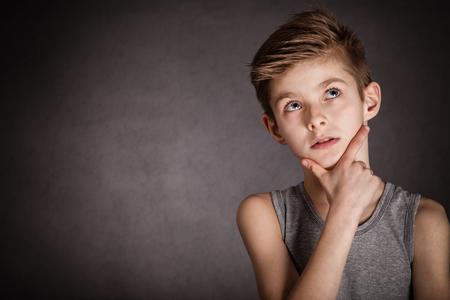 bambini pensierosi: Primo piano premuroso Giovane ragazzo cercando con la mano sul viso su sfondo grigio con spazio di copia