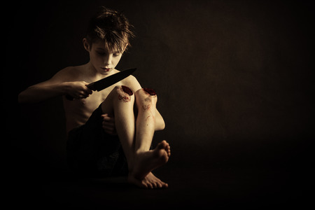 hurting: Psychotic Young Boy with Wounds on his Knees, Hurting Himself with Knife Against Black Background with Copy Space.