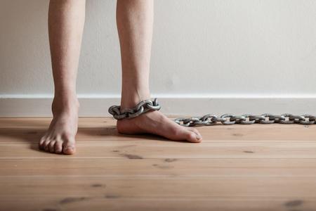 maltrato: Cierre de pies descalzos conceptuales de un muchacho joven con la gran cadena de pie dentro de una habitación