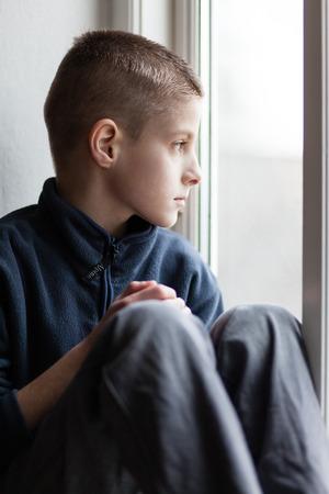 ni�os abandonados: Cierre de solo Orphan Boy que se sienta en el cristal de ventana y mira hacia fuera con la expresi�n facial pensativo. Foto de archivo