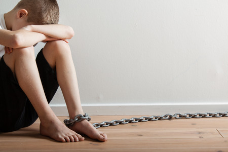 abject: Conceptual Lonely Boy with Chain on his Foot Sitting Inside a Room and Hiding his Face Against White Wall Background with Copy Space. Stock Photo