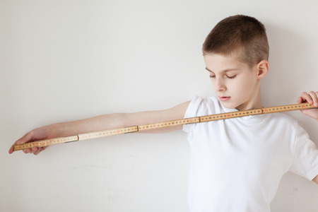 half body: Half Body Shot of a Handsome Young Boy Holding a Meter Stick with One Arm is Stretching Against Plain White Wall Background. Stock Photo