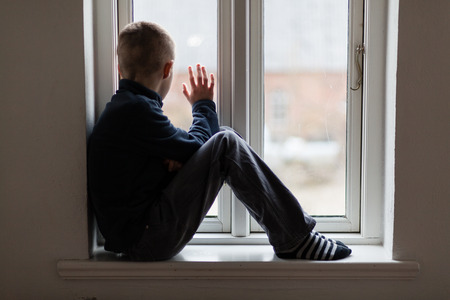 Young boy sitting on a windowsill inside a house waving to someone outside, view from the side