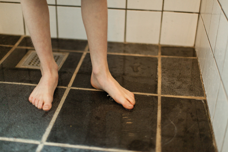 bare feet boys: Bare Feet of a Young Boy Stepping on the Floor with Water Inside the Home Bathroom