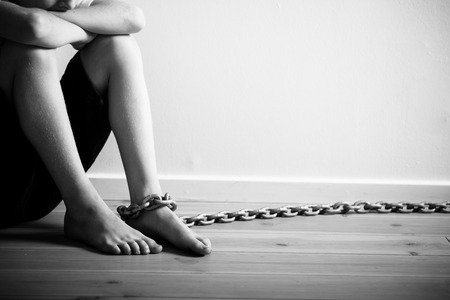 inhumane: Abused Young Boy with Chain on his Foot Sitting Inside a Room Against Plain Wall Background with Copy Space in Monochrome Color.