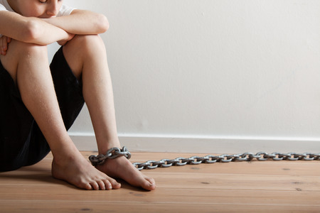 convict: Conceptual Lonely Young Boy Sitting in a Room with Knees Up and Folded Arms, with Big Chain on his Foot Stock Photo